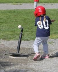 Girl batting at tee ball station